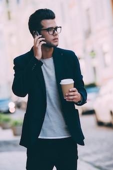 Ik zal op tijd zijn. knappe jongeman in slimme vrijetijdskleding met koffiekopje en pratend op mobiele telefoon terwijl hij over straat loopt