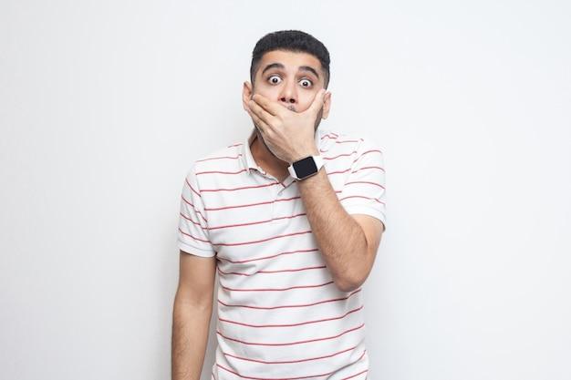 Ik zal stil zijn. portret van een geschokte, bebaarde jongeman in een gestreept t-shirt die zijn mond met handen sluit en met grote ogen naar de camera kijkt. indoor studio opname, geïsoleerd op een witte achtergrond.
