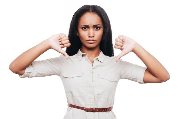 Ik zeg nee! zelfverzekerde jonge afrikaanse vrouw die haar duimen naar beneden houdt terwijl ze tegen een witte achtergrond staat
