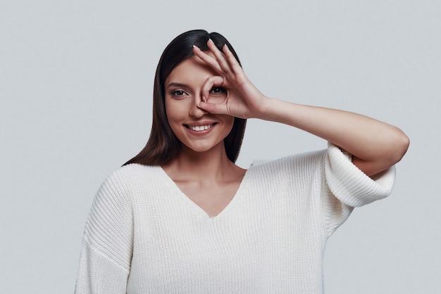 Ik zie je! aantrekkelijke jonge vrouw die naar de camera kijkt en glimlacht terwijl ze tegen een grijze achtergrond staat