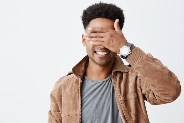Ik zie je niet. sluit omhoog portret van de jonge aantrekkelijke donkere gevilde mens met afrokapsel in het toevallige de herfst siling, sluitende ogen met hand, spelend met weinig kind op straat.