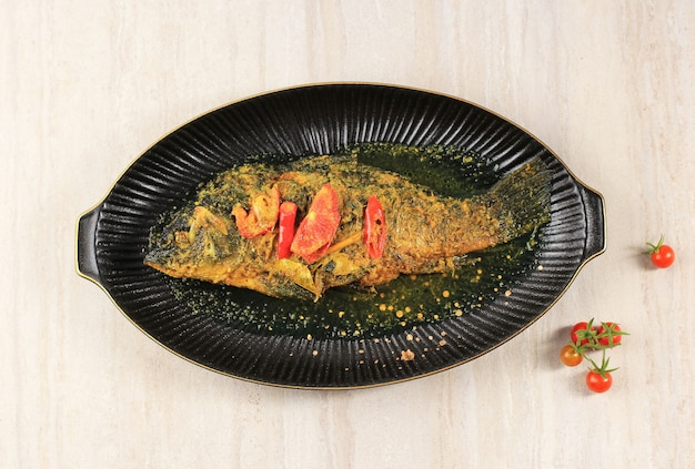 Ikan pesmol of pesmol-vis met gele curry, bovenaanzicht met kopieerruimte voor tekst
