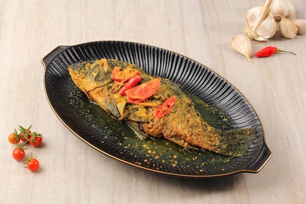Ikan pesmol of pesmol vis met gele curry, close-up op houten tafel met kopie ruimte voor tekst