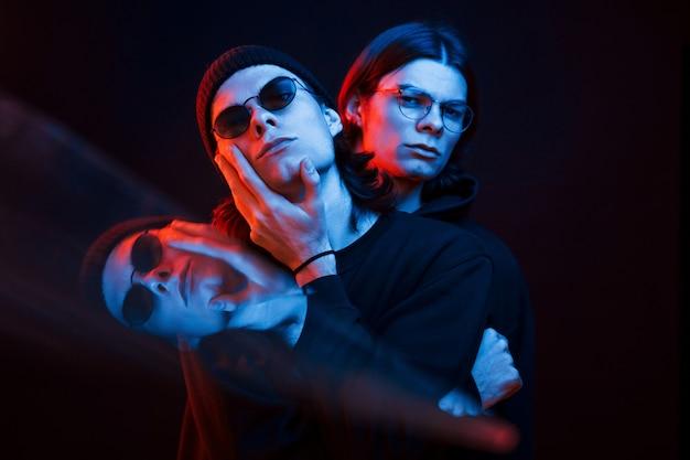Illusie van drie gezichten. portret van tweelingbroers. studio opname in donkere studio met neonlicht