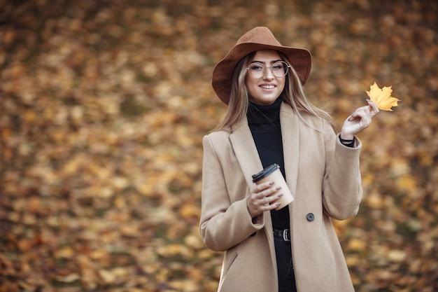 Image-shot van een jonge aantrekkelijke vrouw gekleed in een jas en vilten hoed op de achtergrond van gevallen bladeren in het herfstpark