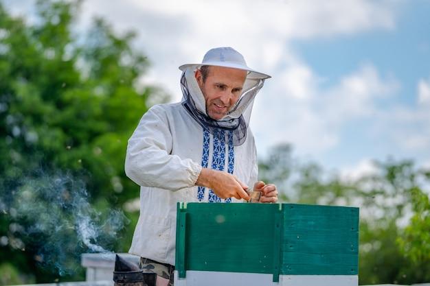 Imker bij bijenstal op de zomerdag. man aan het werk in bijenstal. bijenteelt. bijenteelt concept.