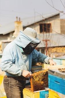 Imker werkt met bijen en inspecteert bijenkorf na de winter