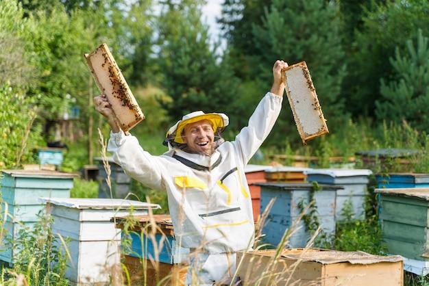 Imker werkt met bijen in de bijenstal