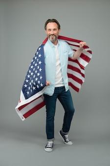 Immigratie naar de vs. volwassen man houdt amerikaanse vlag vast. visum voor immigratiereizen. amerikaanse groene kaart. verenigde staten permanente verblijfsvergunning. staatsburgerschap en immigratie. immigratie- en naturalisatiedienst.