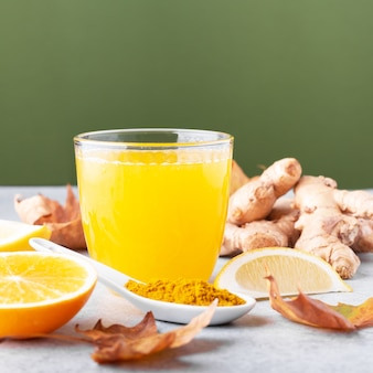 Immuunversterkende drank met citrusvruchten, gember, kurkuma. drink of smoothie met gele herfstbladeren voor de herfst of het virusseizoen op een neutrale beige achtergrond, stilleven