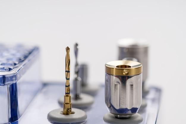 Implanteer chirurgische uitrustingen die beetjes op witte achtergrond boren.