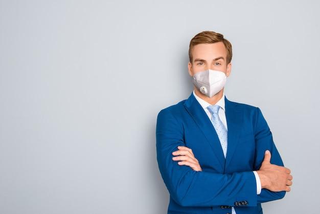 Imposante man met herbruikbaar ademhalingsmasker gevouwen arm