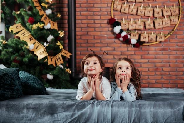 In afwachting van geschenken. wat ze twee vrolijke vrouwelijke kinderen liggend op het bed met nieuwjaar decoraties en vakantie boom