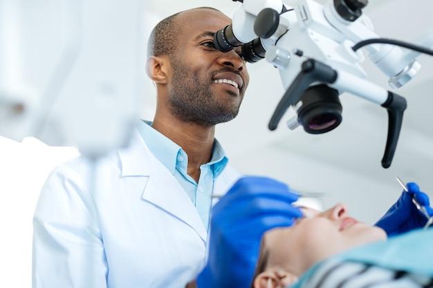 In alle details onderzoeken. vrolijke jonge mannelijke tandarts die een professionele microscoop met behulp van en een controle van de mondholte van zijn patiënten uitvoert