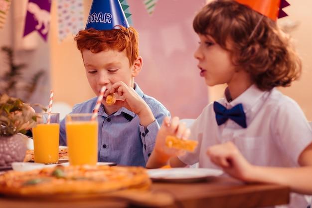 In alle oren. vrolijke brunette jongen hoofd draaien tijdens de communicatie met zijn klasgenoten