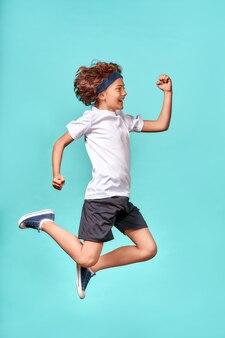 In beweging, verticaal schot van volledige lengte van een vrolijke, energieke tienerjongen die geïsoleerd over blauw springt