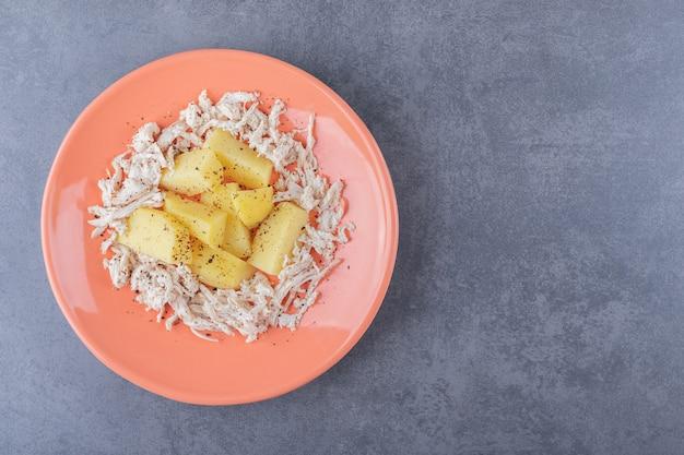 In blokjes gesneden kip met gekookte aardappelen op oranje plaat.