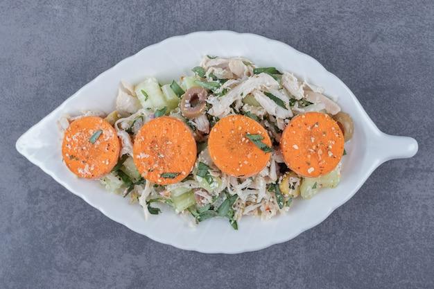 In blokjes gesneden kippensalade op bladvormige plaat.