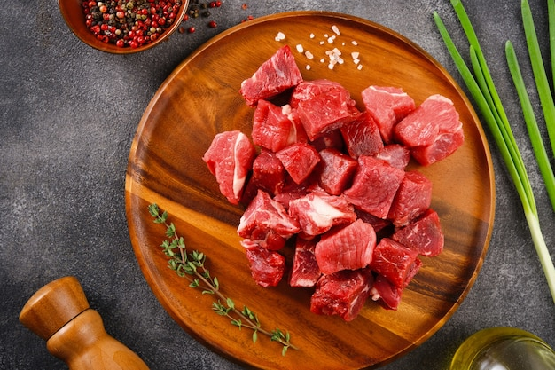In blokjes gesneden rauw rundvlees op een houten bord, specerijen, kruiden en groenten op donkergrijze achtergrond. grondstoffen voor goulash. bovenaanzicht.