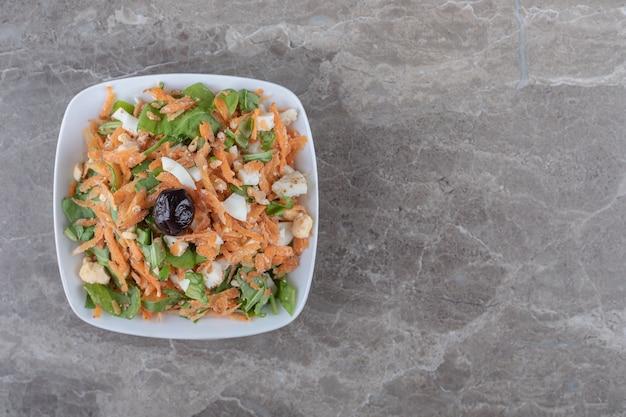 In blokjes gesneden wortelen en groentesalade in witte kom.