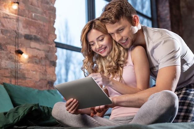 In comfortabel bed. stralend pas getrouwd stel zittend in hun comfortabele bed en tablet gebruikend tijdens het kijken naar film