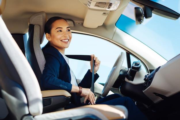 In de auto. gelukkige positieve vrouw die lacht tijdens het vastmaken van de veiligheidsgordel