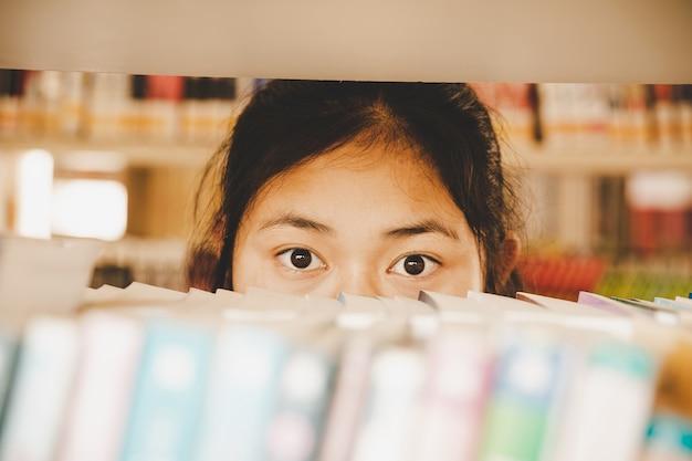 In de bibliotheek - jonge studente met boeken die in een middelbare schoolbibliotheek werken.