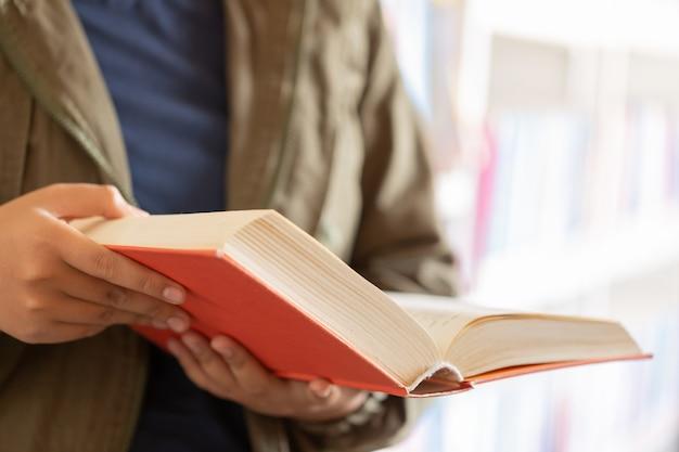 In de bibliotheek - tienerstudent met boeken die in een middelbare schoolbibliotheek lezen.