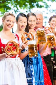 In de biertuin - vrienden, man en vrouw in tracht, dirndl en lederhosen die een vers biertje drinken in beieren, duitsland
