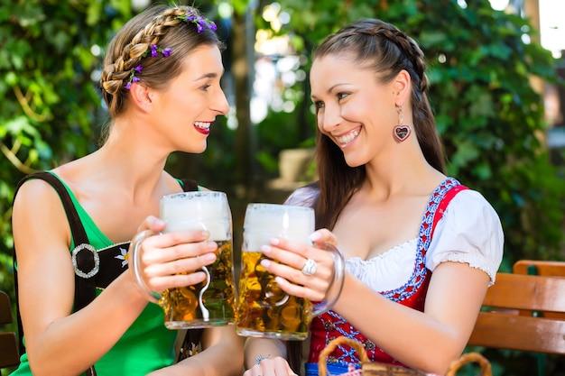 In de biertuin - vriendinnen in tracht, dirndl en lederhosen drinken een vers biertje in beieren, duitsland