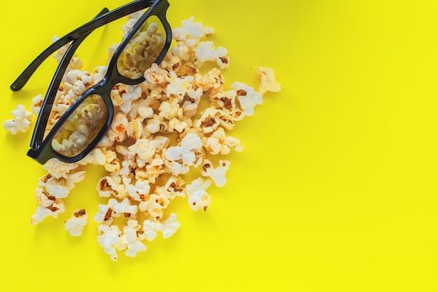 In de bovenhoek is er een bril op popcorn op een gele achtergrond bovenaanzicht plat lag kopieerruimte...