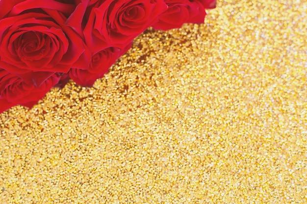 In de bovenhoek van de foto staat een boeket rode rozen op een heldere gouden achtergrond bovenaanzicht...