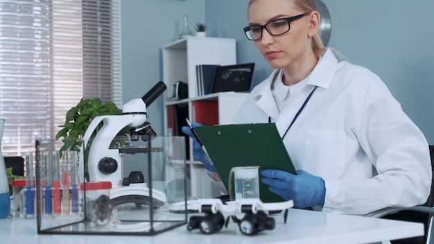 In de chemie laboratoriumonderzoek wetenschapper die waarnemingen van laboratoriumhamster doet