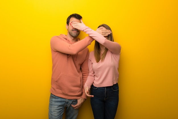 In de dag van de valentijnskaart groep van twee mensen op gele achtergrond die betrekking hebben op ogen door handen. verrast om te zien wat er gaat gebeuren