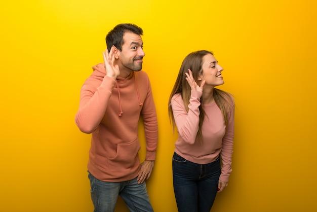 In de dag van de valentijnskaart groep van twee mensen op gele achtergrond luisteren naar iets door hand op het oor te zetten