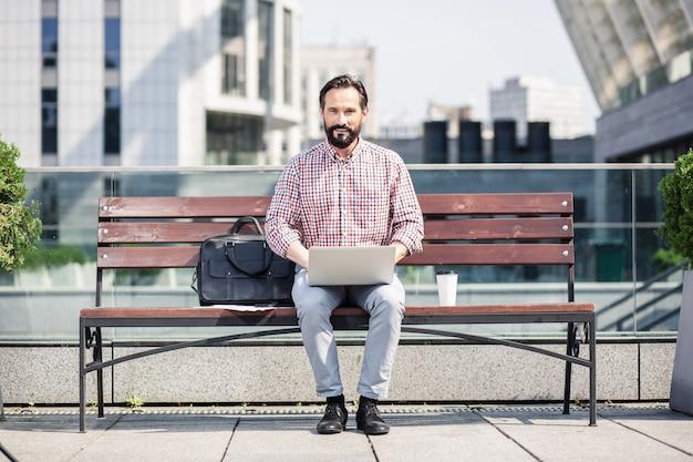In de frisse lucht. aangename glimlachende man die zijn laptop gebruikt terwijl hij op de bank zit