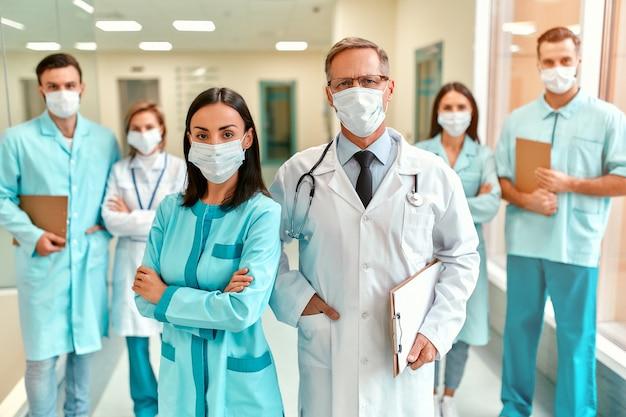 In de gang van de kliniek staat een succesvol team van artsen met beschermende medische maskers. bescherming in quarantaine en covid-19.