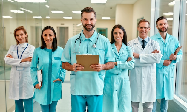 In de gang van de kliniek staat een succesvolle, vrolijke groep fulltime artsen, medisch personeel met een stethoscoop en patiëntendossiers.