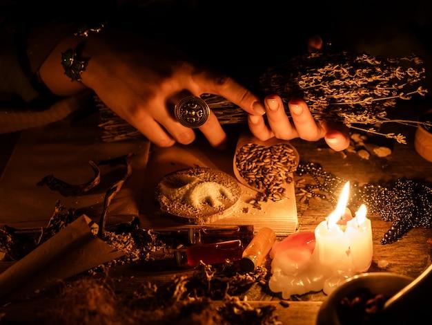 In de handen van de heksen een bos droge kruiden voor waarzeggerij. het licht van de kaarsen op de oude magische tafel. kenmerken van occultisme en magie.