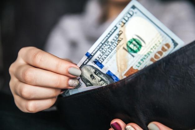 In de handen van de vrouwen ligt de bruinleren portemonnee met een prop van honderd dollar. zakelijk aanbod. mooie manicure