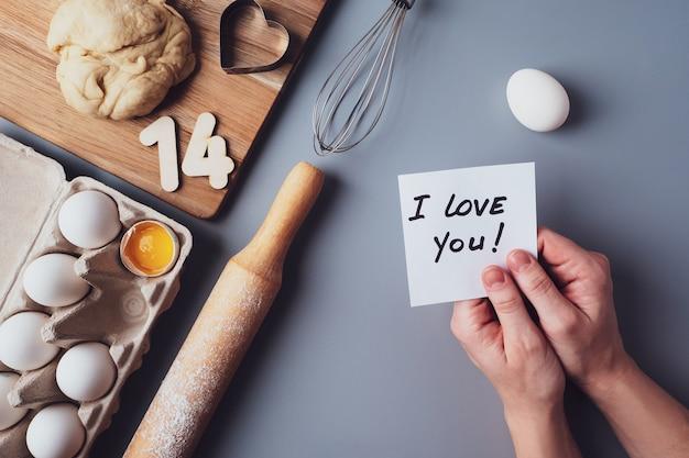 In de handen van een briefje hou ik van je. ingrediënten voor het maken van zelfgemaakte koekjes op een grijze achtergrond. het concept van het koken van snoep voor valentijnsdag, vaderdag of moederdag. plat lag, bovenaanzicht.