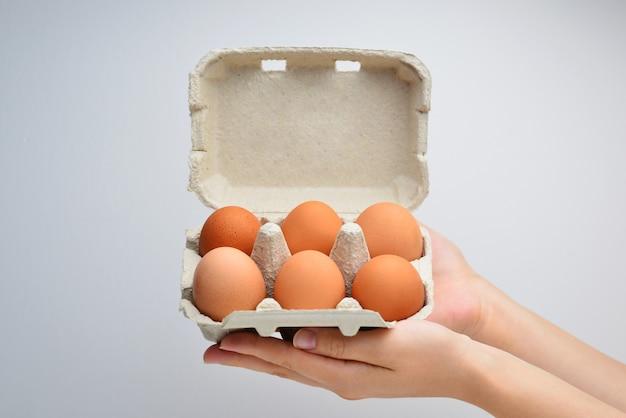 In de handen van een vrouw die eieren inpakt op een witte geïsoleerde achtergrond