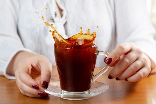 In de handen van het meisje een kopje koffie. koffiespray. splash mooie vormen van koffiespatten. rode manicure. zonnige ochtend. ontbijt tijd. concept