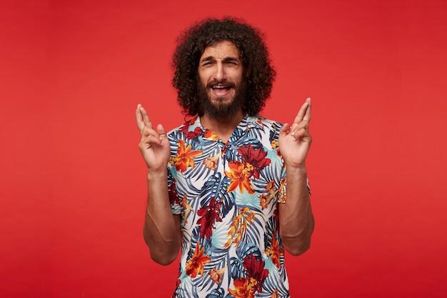 In de hoop dat een vrij positieve jonge, bebaarde man met krullend bruin haar handen opheft met gekruiste vingers en wensen doen, fronsende wenkbrauwen en mond openhouden, geïsoleerd op rode achtergrond
