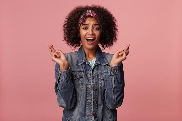 In de hoop dat jonge, vrij donkere gekrulde vrouw met kort bruin haar, kleurrijke hoofdband en vrijetijdskleding draagt, wens doet en vingers kruist voor geluk