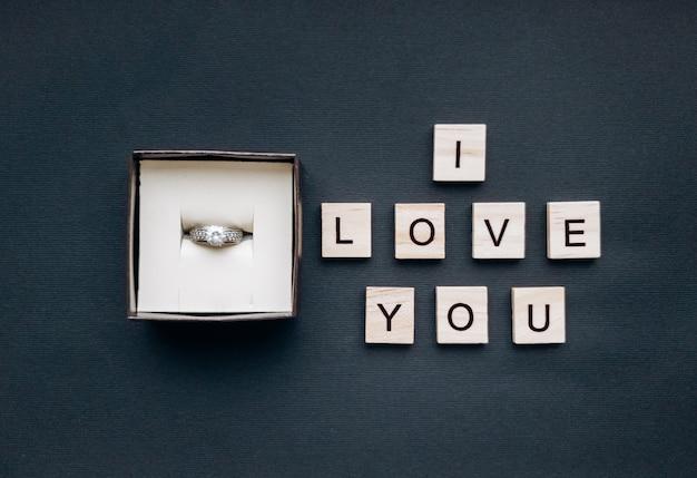 In de juwelendoos zit een ring met een steen en een inscriptie van houten vierkanten ik hou van je op een mooie zwarte achtergrond. romantisch begrip. platte stijl.