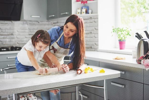 In de keuken en gelukkige familie. concept vakantie voedsel. de moeder en de dochter die het deeg voorbereiden, bakken koekjes. gelukkige familie in het maken van cookies thuis. zelfgemaakt eten en kleine helper