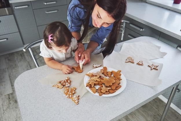 In de keuken en gelukkige familie. concept vakantie voedsel. moeder en dochter versieren koekjes. gelukkige familie bij het maken van zelfgemaakte gebak. zelfgemaakt eten en kleine helper