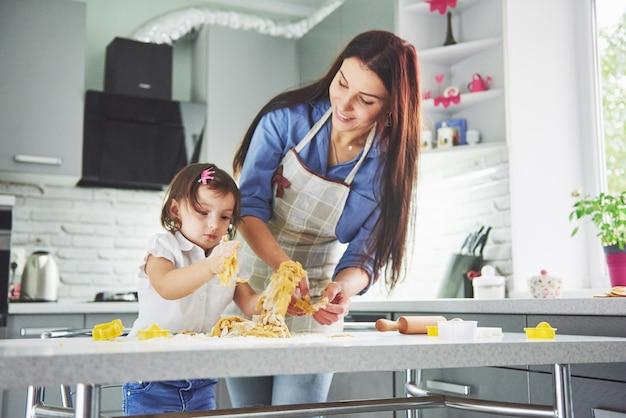 In de keuken en gelukkige familie. de moeder en de dochter die het deeg voorbereiden, bakken koekjes.