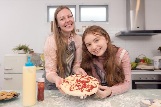 In de keuken thuis schreeuwen een speelse moeder en dochter terwijl ze pizzadeeg maken.